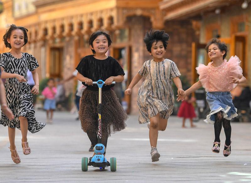 孩子们在新疆和田市鸽子巷奔跑玩耍(5月27日摄)。