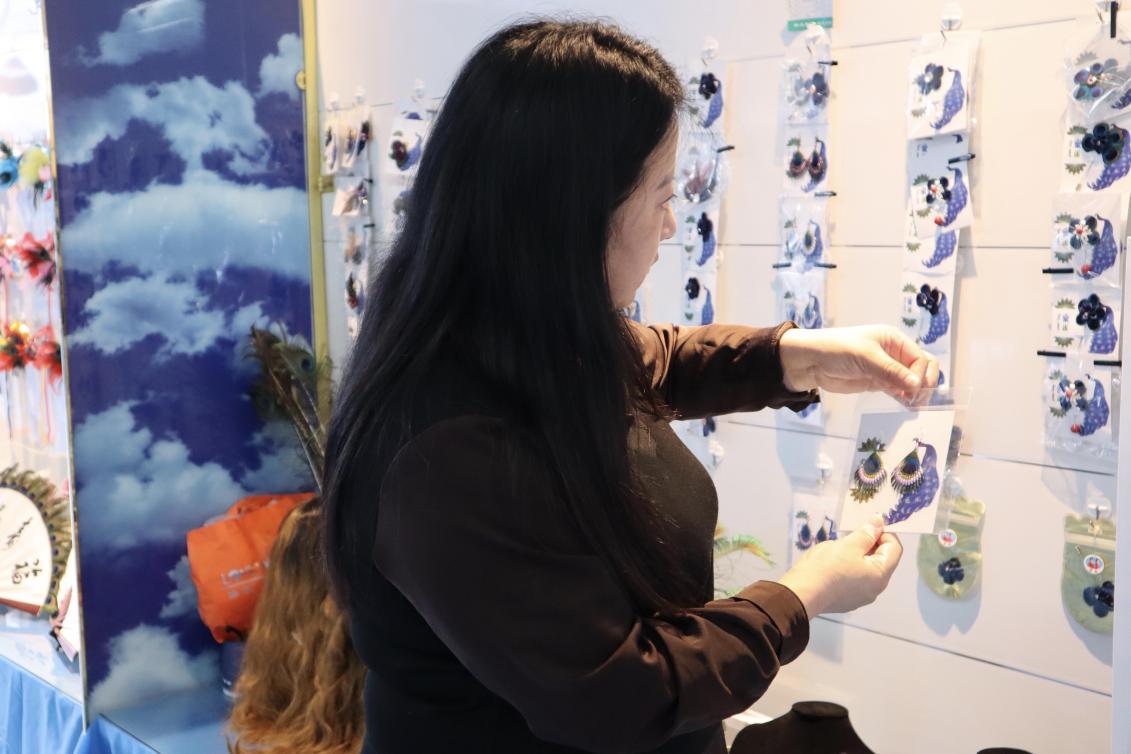 (周海燕在展示孔雀羽毛工艺品制作 央视网记者 王静远 摄)